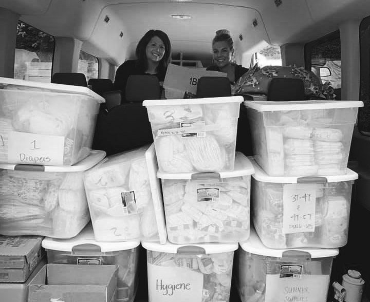 Plastic boxes full of diapers and other necessities stocked up in the back of the babies of homelessness van. Two volunteer women stand behind them.