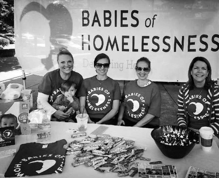 Four volunteer women sit at a table with a babies of homelessness banner behind them and promotional materials on the table.